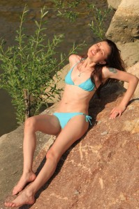 Beautiful Girl Sunbathing on a Rock